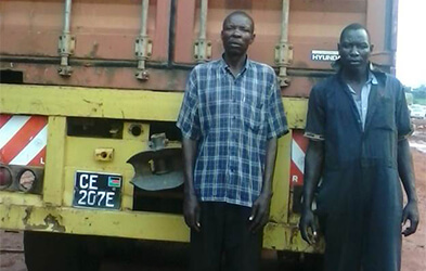John Muteba and his colleague stand outside their vehicle